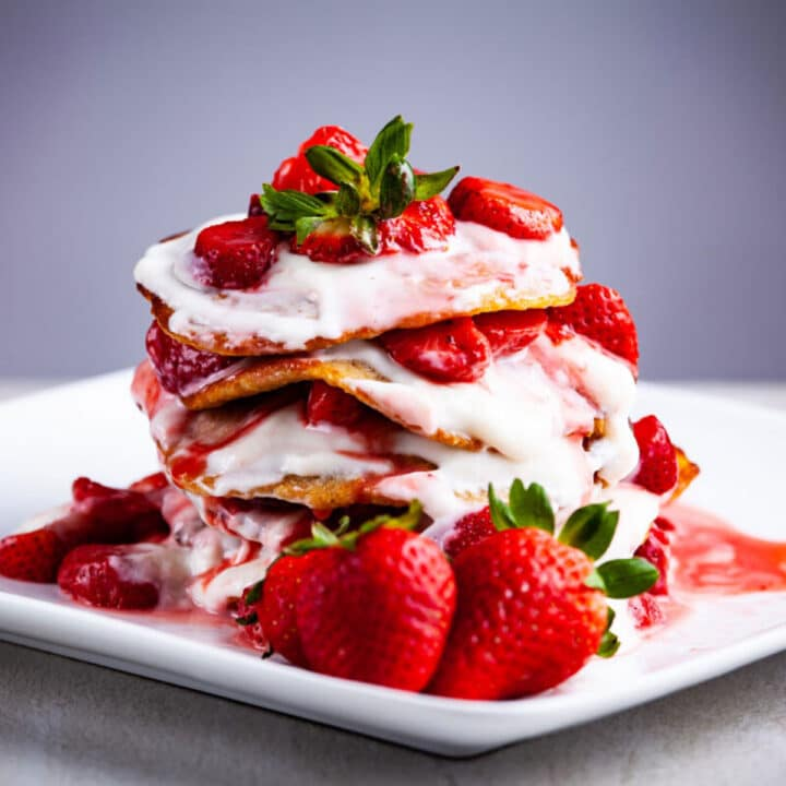 Pancakes stacked on top of each other and topped with strawberries and goat yogurt.
