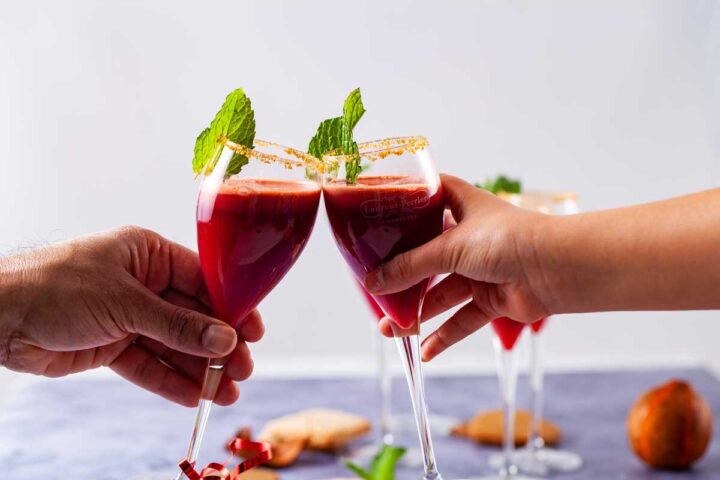 A close up of two hands toasting with a garnished red non alcoholic drink.