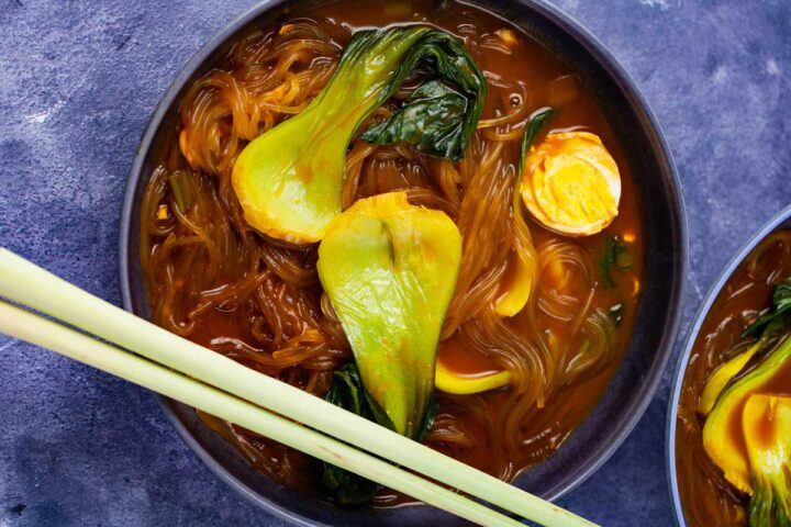 A bowl filled with bok choy noodle soup topped with half of a cooked egg and lemon grass stalks shown like chop sticks.