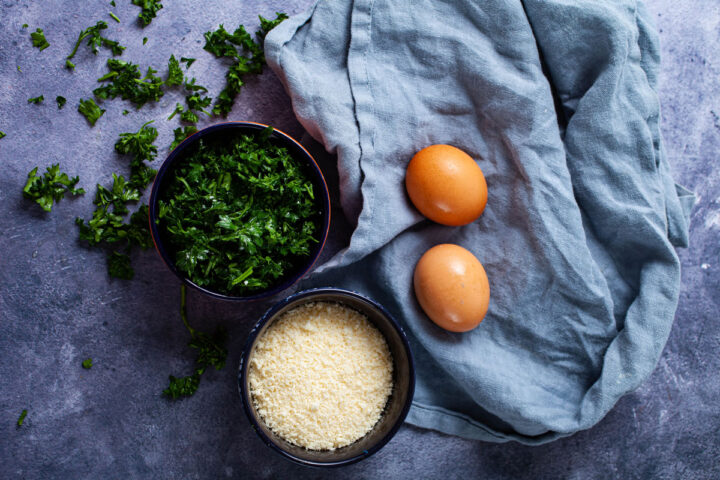 A small bowl with grated parmesan cheese, another small bowl with chopped fresh Parsley, and two fresh farmers eggs on a towel.