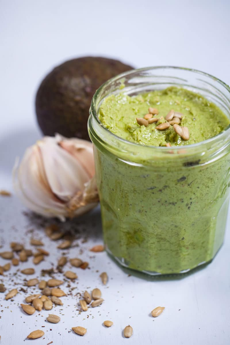 A jar filled with Basil pesto next to its ingredients