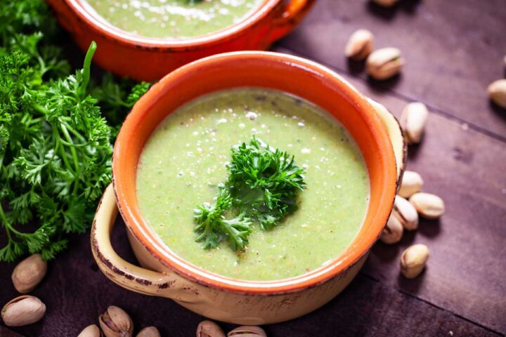 A close-up of a terra cotta bowl filled with green pea soup, topped with fresh Parsley leaves.