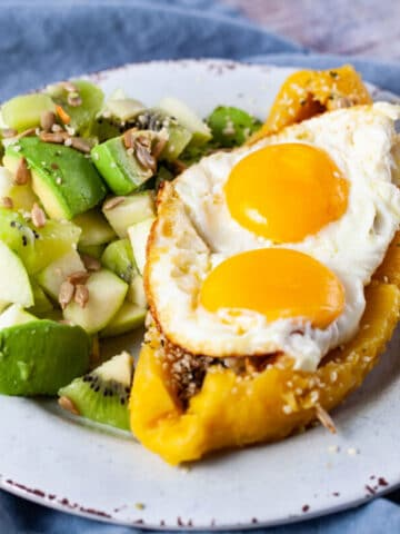An opened cooked plantain filled with eggs and seeds next to a green fruit salad.
