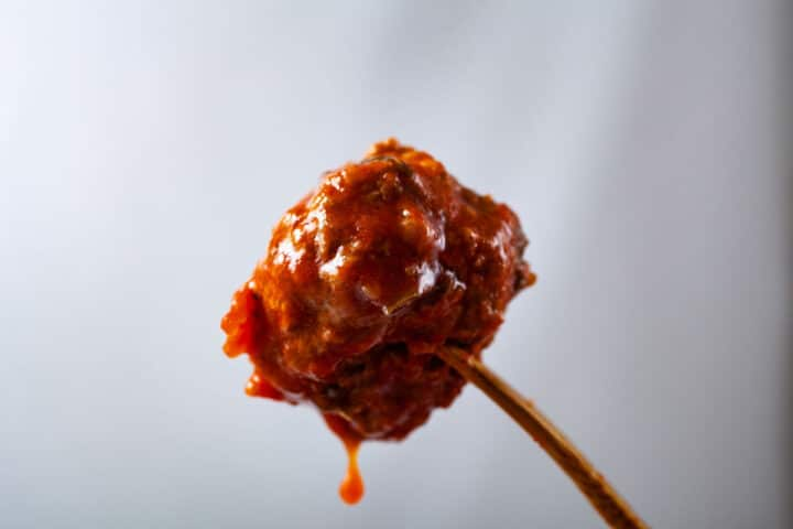 A wooden fork pierced into a juicy meatball.
