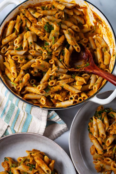 A table with a large white pan filled with creamy pasta next to two plates also filled with the same food.