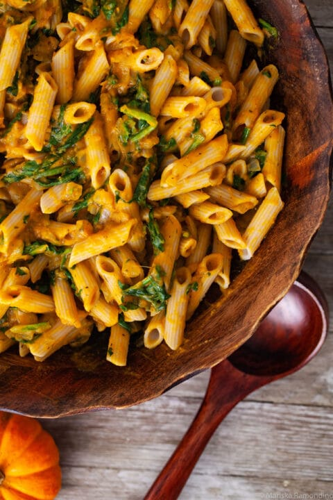 A close-up of a large wooden bowl filled with creamy pasta and spinach.