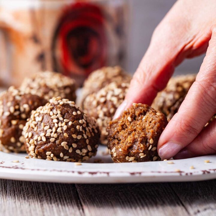 A hand placing half of an energy ball sprinkled with seeds on a small plate next to other sesame seeds sprinkled energy bites.