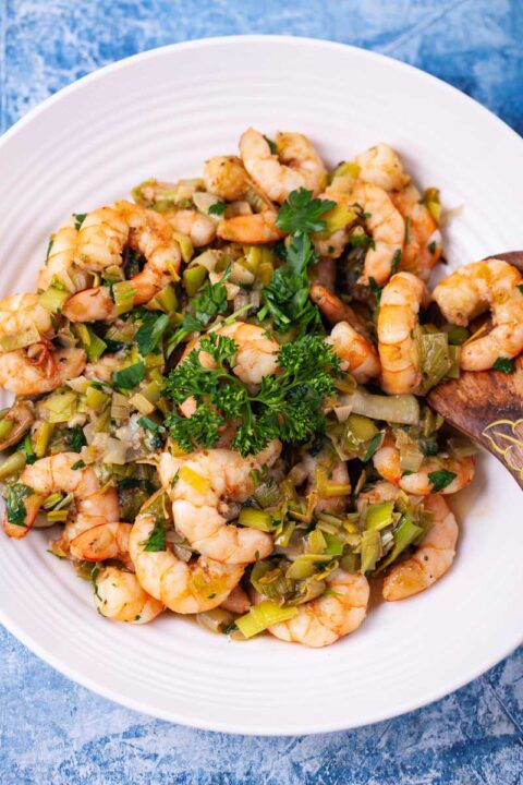 A large plate with spiced and garlicky shrimp and leeks plus fresh parsley garnish.