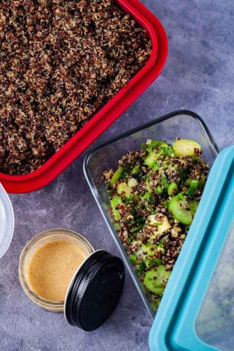 Tupperware filled with cooked red quinoa, next to a jar filled with a dressing and another container filled with avocado quinoa salad.
