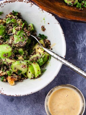 A small bowl filled with avocado quinoa salad and a creamy lemon dressing on the side.