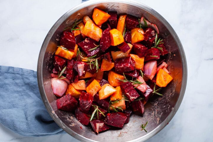 A large bowl filled with raw cubed beets, onions, and potatoes and seasoned with herbs.