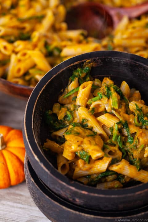 A close-up of two stacked wooden bowls with the bowl on top filled with a pumpkin spinach pasta.