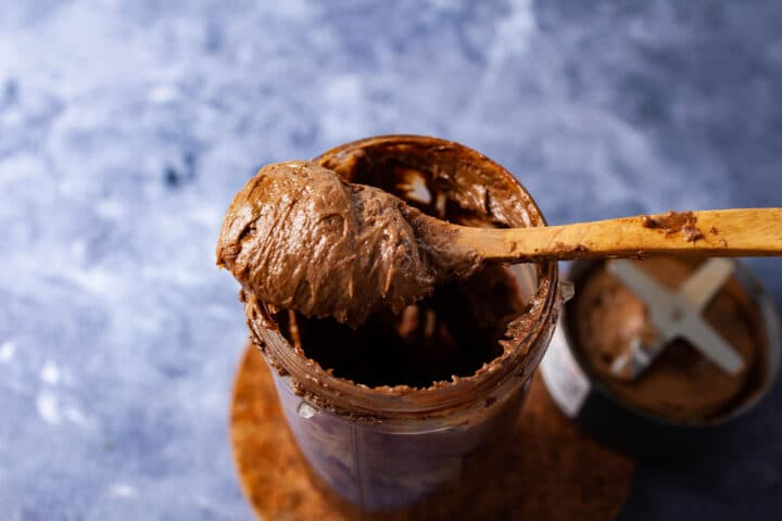 A spoon generously filled with chocolate pudding and resting on a large jar also filled with the same pudding.