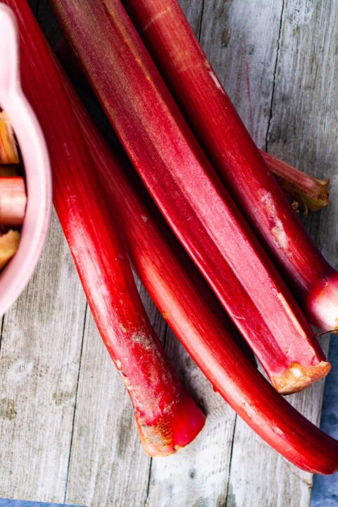 Five large red rhubarb stalks resting on a wooden board.