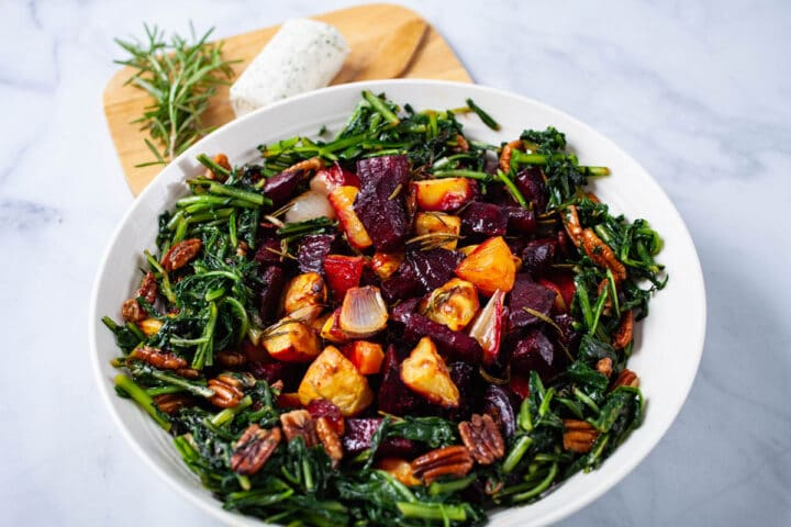 A large plate filled with roasted beets, potatoes, sauteed dandelion greens, pecans, next to a wooden plate topped with extra goat cheese and Rosemary.