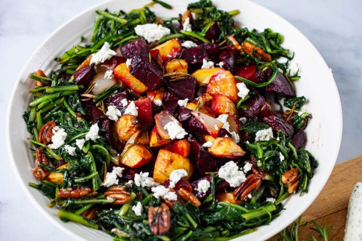 A large plate filled with roasted beets, potatoes, sauteed dandelion greens, pecans, topped with goat cheese.