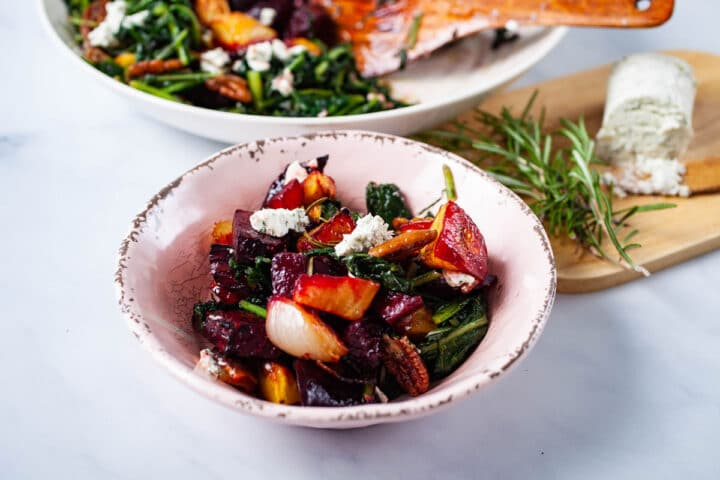 A small plate filled with roasted beets, potatoes, sauteed dandelion greens, pecans, topped with goat cheese, with a wooden plate with extra goat cheese and Rosemary in the background.