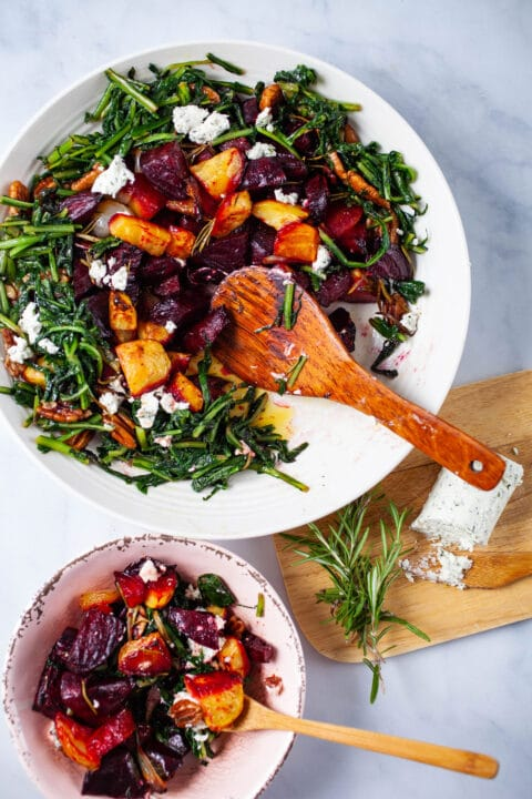 A large plate filled with roasted beets, potatoes, sauteed dandelion greens, pecans, topped with goat cheese, and next to a wooden plate with extra goat cheese and Rosemary.