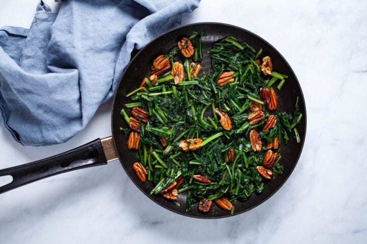 A medium-sized pan, filled with sauteed dandelion greens and pecans.