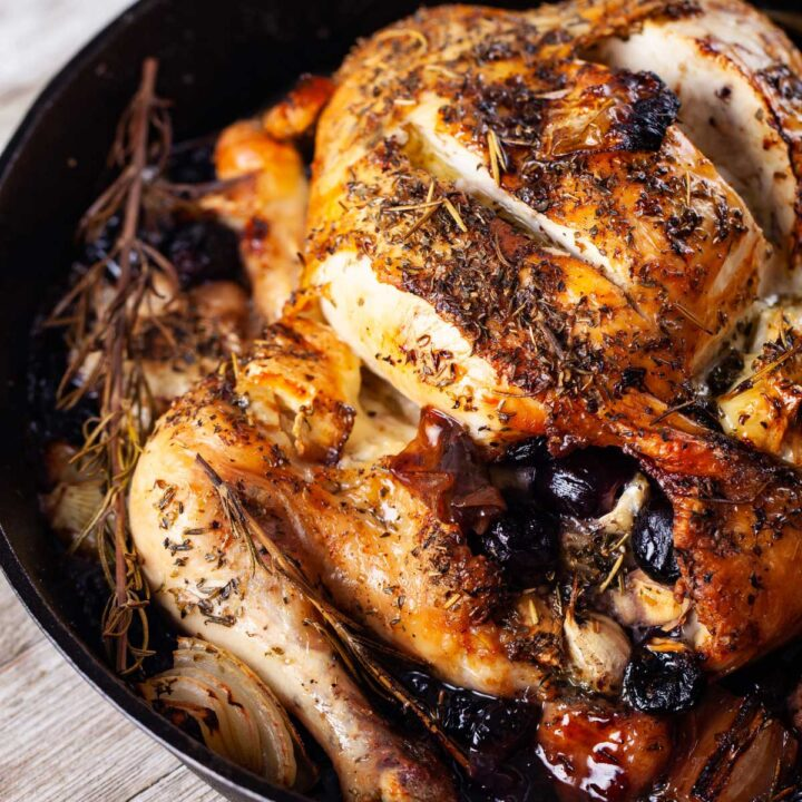Whole roasted chicken in an iron skillet filled with brie, grapes and seasoned with rosemary.