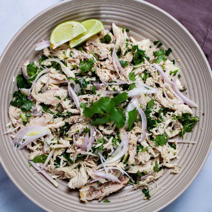 A large deep plate filled with shredded chicken salad with cilantro, olive oil, shallots, salt and pepper, and lime wedges on the side.