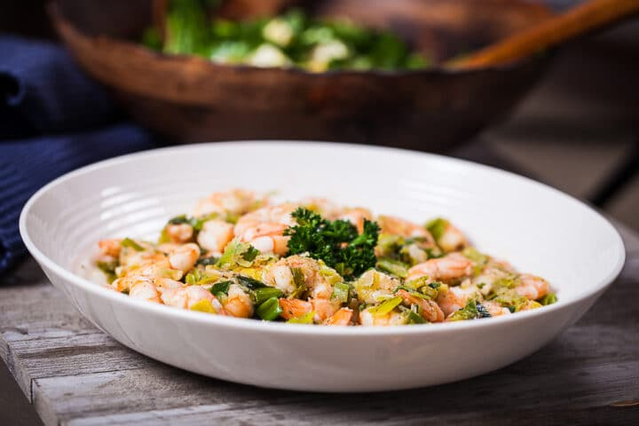 A large white plate filled with sauteed shrimp and leeks, placed on a wooden table.