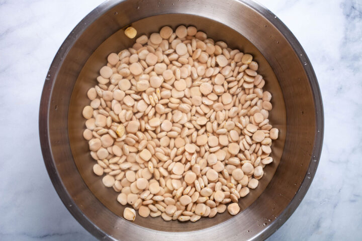 A bowl filled with uncooked Lupini beans and submerged in water.