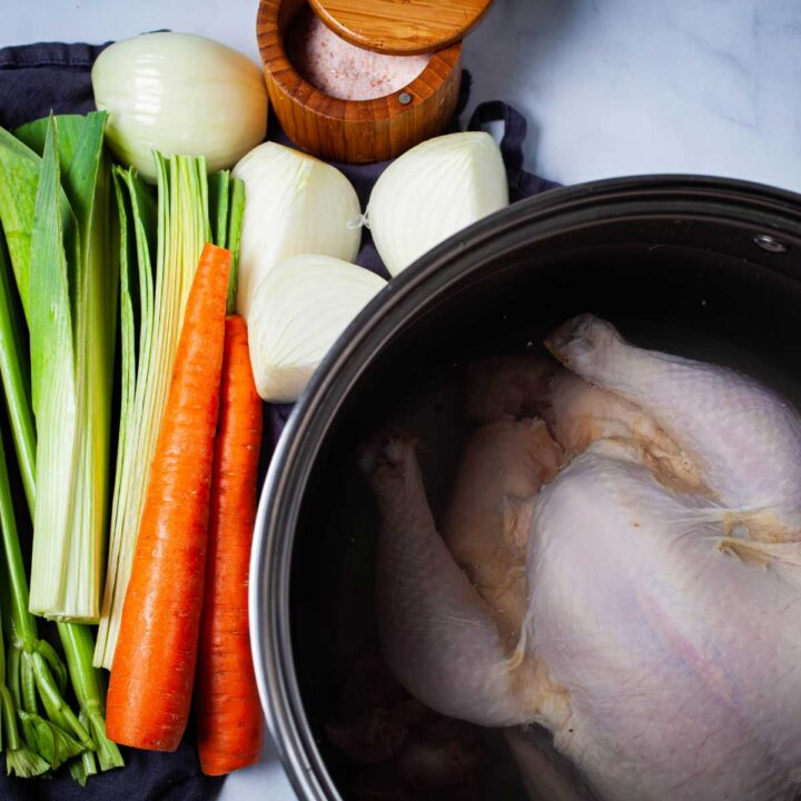 A large pot containing a whole raw chicken covered with water, next to fresh chopped vegetables like celery, leek, carrots, onions, and a pot of salt.