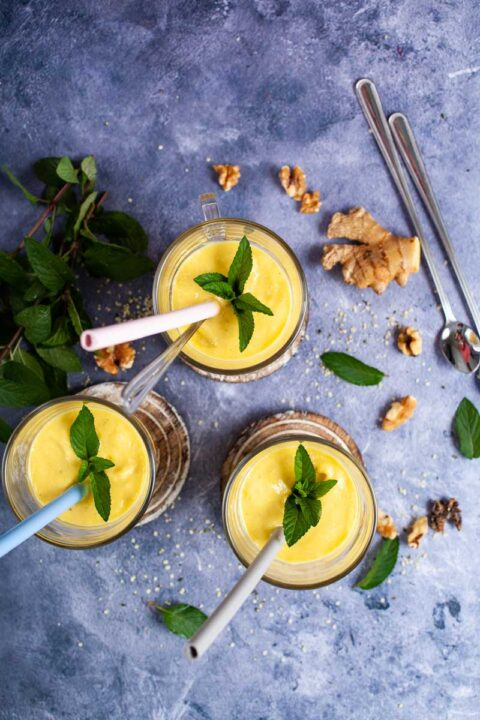 Three glasses filled with mango lassi, topped with mint leaves and each carrying a straw.