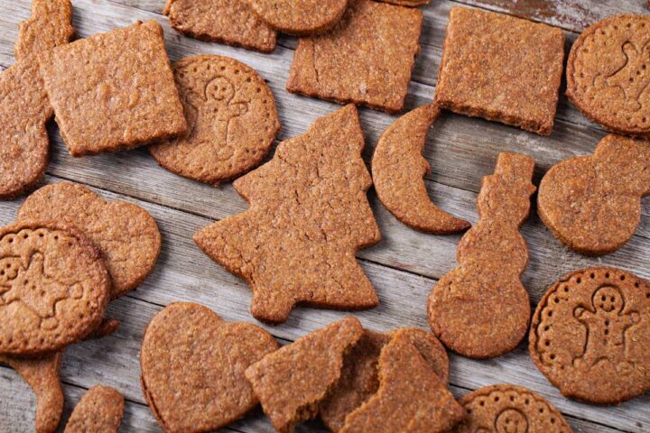 Shaped speculoos cookies laid out on a wooden table.