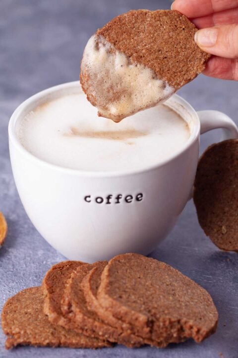 A hand having dipped a cookie in a latte.