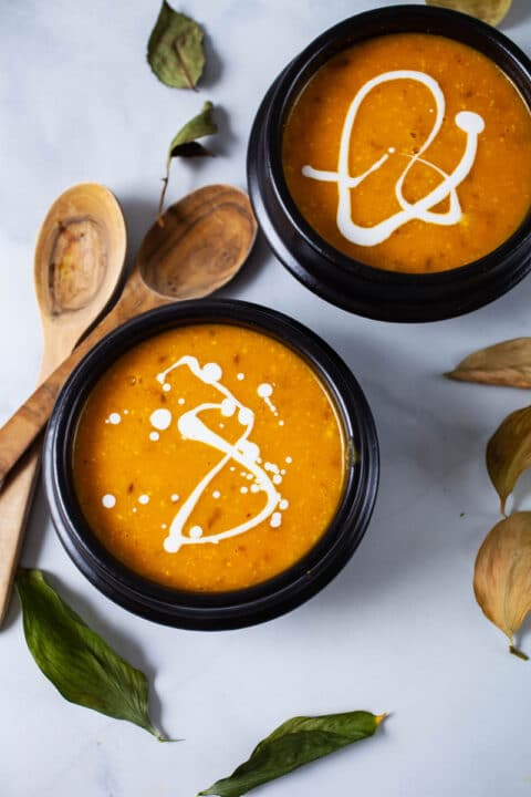 Two bowls filled with squash soup and topped with coconut cream.