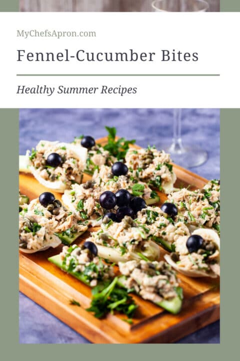 Fresh cucumber and fennel slices topped with tuna salad and garnished with dark grapes neatly presented on a wooden board and text overlay.
