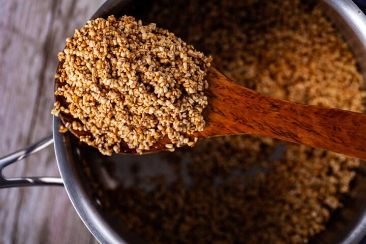 A large wooden spoon holding toasted oats and resting on top of a pan filled with toasted oats.