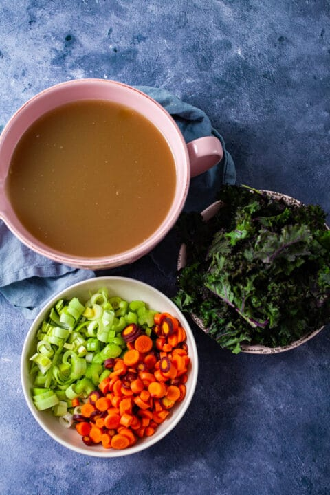 A large bowl with chicken stock, another bowl with chopped fresh veggies like carrots, leeks, and celery, and another bowl with chopped kale on a table.