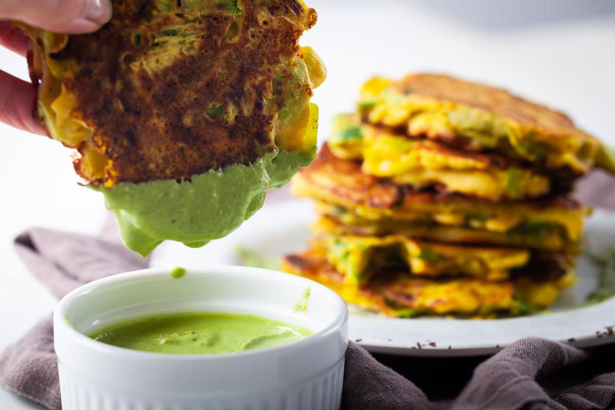Vegetable fritter dipped in avocado pesto sauce