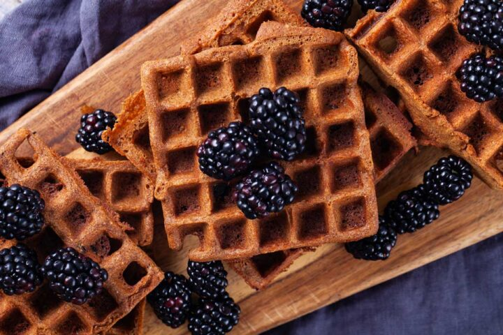 Golden brown waffles stacked on a wooden board and topped with fresh blackberries.