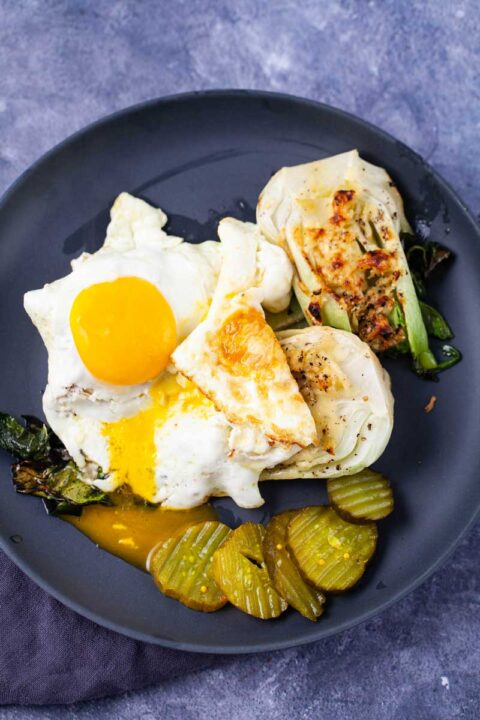 Two eggs sunny side up topped on roasted Chinese cabbage and served with pickles on the side.