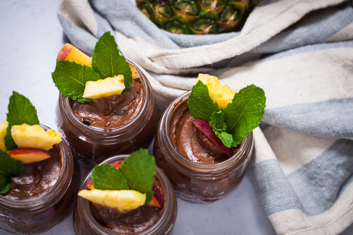 Delicious chocolate avocado pudding swirled in small cups and topped with fresh fruits and mint leaves