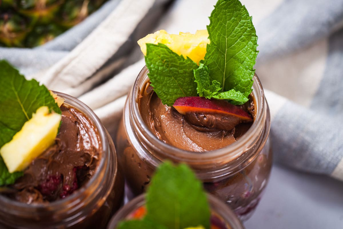 Close up of avocado pudding in small jar topped with fresh fruits and fresh mint leaves.