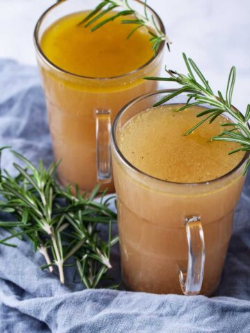 Two cups filled with broth and topped with fresh Rosemary leaves.