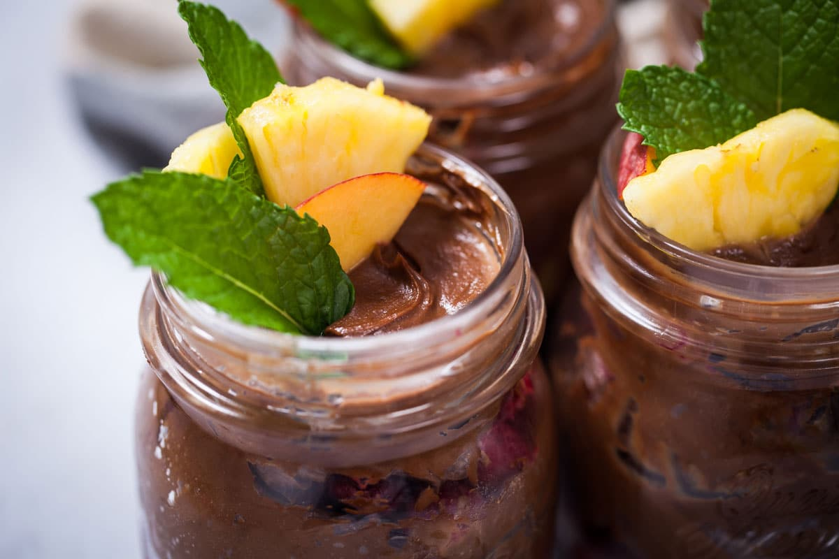 Creamy avocado chocolate pudding in a cup garnished with fresh fruits and mint leaves