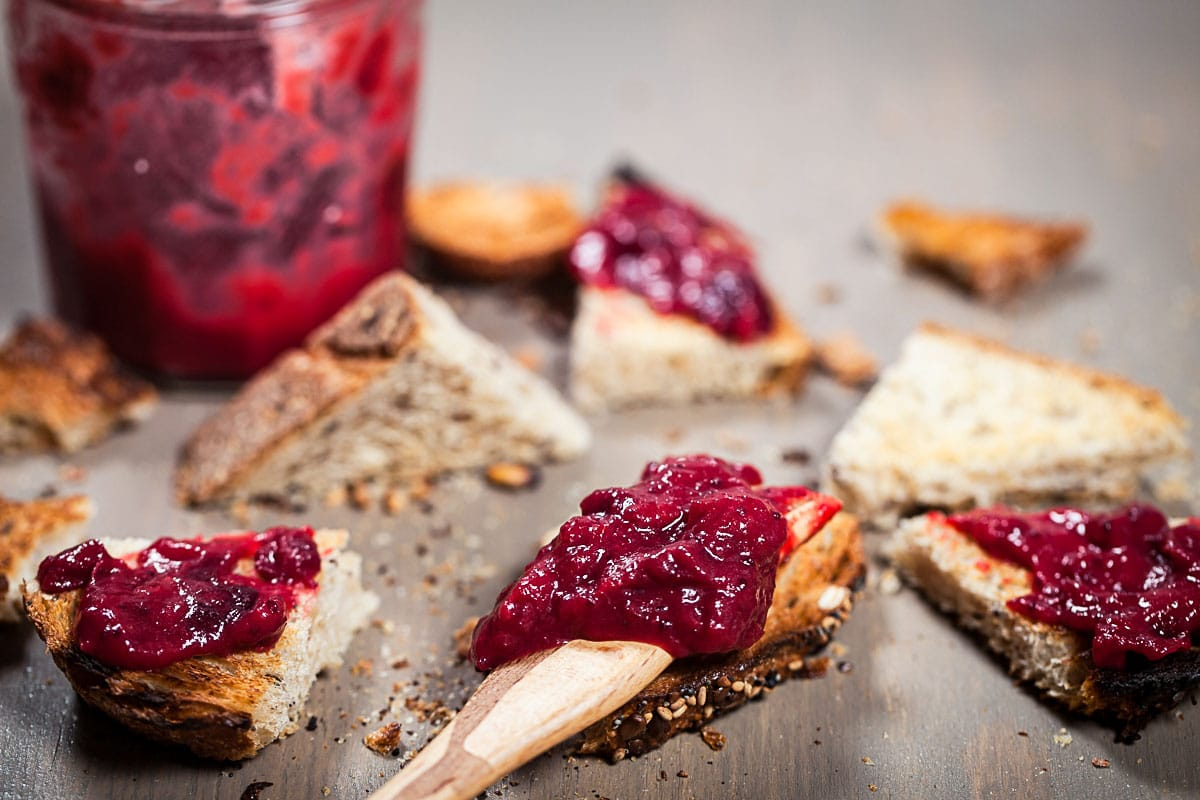 A wooden knife carrying cranberry jam resting on top of a piece of toast.